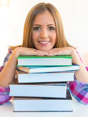 Smiling student with stack of books