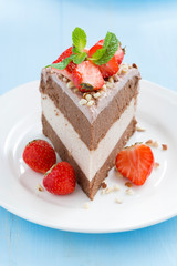 piece of chocolate cake of three layers with fresh strawberries