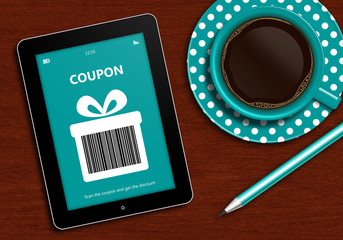 tablet with discount coupon and  cup of coffee lying on desk