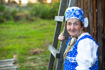 Old woman posing at village in folk costume.