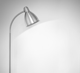 Metal floor lamp standing near white wall