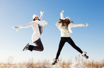 Two girlfriends have fun and enjoy fresh snow at beautiful winte