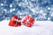 Two red gift boxes in snow on abstract background