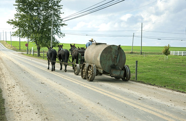 Amish horse drawn tank being pulled along road.