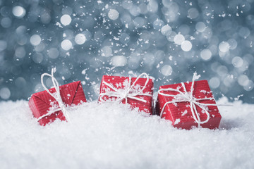 Three red gift boxes in snow on abstract background