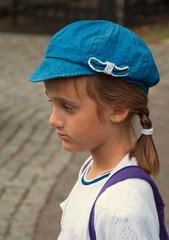 Profile portrait of sad girl in a blue cap