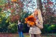 woman is holding the leaves in autumn
