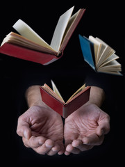 Books flying from hands, on black background