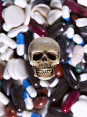 Skull in the pile of drugs. Sickness and danger of abuse