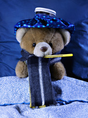 A sick teddy bear with a thermometer