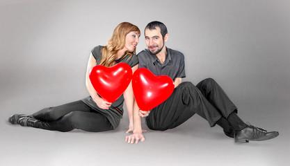 couple with heart balloon sitting in studio