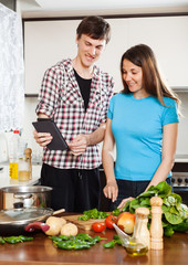 Young couple cooking with eBook