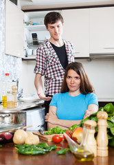 Sad woman listening to man at home kitchen