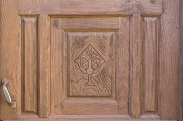 Old brown run-down religious decorated wooden door