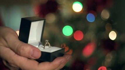 Engagement Ring Proposal Close Up. Christmas Tree Background