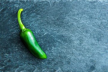 Closeup on green chili pepper on stone substrate