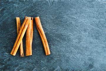 Closeup on cinnamon sticks on stone substrate