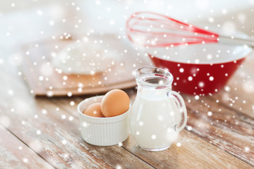 close up of milk jug, eggs, whisk and flour
