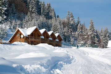 Wooden cottage near the forest, snow at roof, skiers