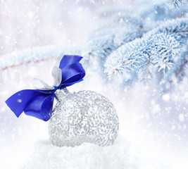 Christmas silver decoration on a background snow-covered fir bra