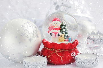 A snow globe with snowman and Christmas decorations