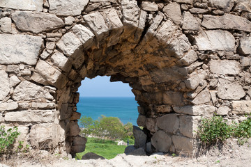 Window in fortification wall, view of sea, green trees and grass
