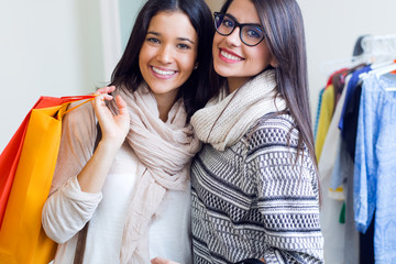 Two beautiful girls shopping in a clothes shop.