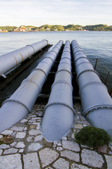 View of old sewage pipes leading to a river.