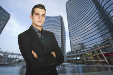 Young businessman with serious expression outside his office