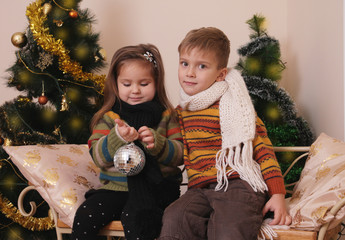Sister and brother playing under golden Christmas tree