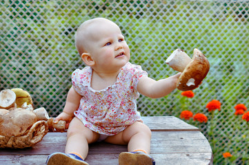 Baby girl sits on the wooden table and holding boletus