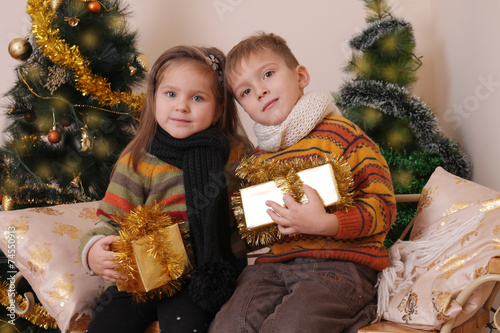 canvas print picture Sister and brother with golden presents under Christmas tree