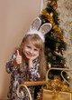 Girl with rabbit ears showing ok over Christmas tree