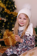 Girl in knitted hat with Christmas golden gift