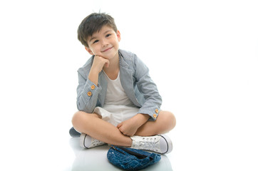 Cute boy sitting on white background