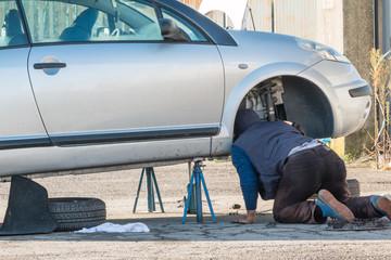 Male mechanic working under car