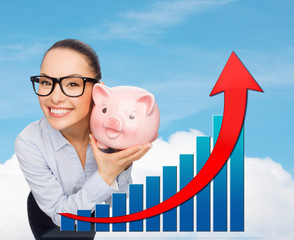 happy businesswoman in eyeglasses with piggy bank