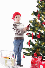 Boy as Santa helper decorating Christmas tree