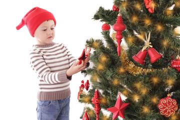 Boy as Santa helper decorating Christmas tree