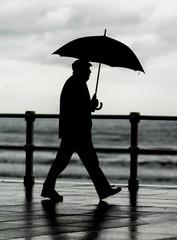 Hombre con paraguas paseando por la ciudad