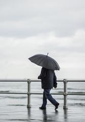 Hombre con paraguas paseando