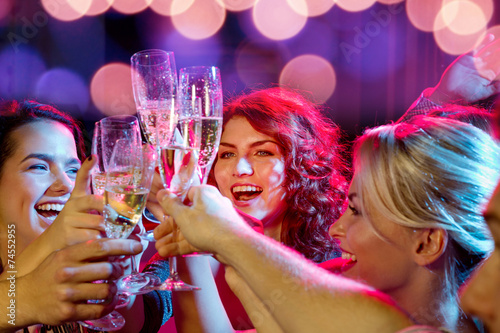 canvas print picture smiling friends with glasses of champagne in club