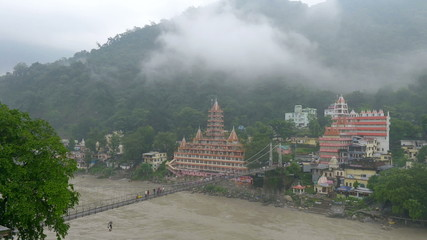 View Ganges River in Rishikesh and people walking across bridge