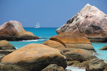 Beach in front of the Seychelles white sail boat sails off the c
