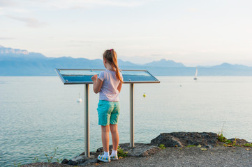 Little girl reading a map with Haute-Savoie Alps