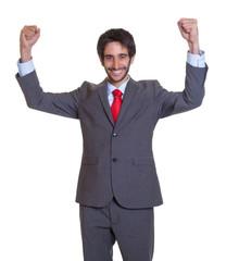Mann mit Anzug und Bar reisst die Arme hoch