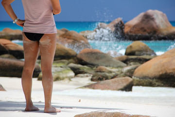 Girl on the beach in front of the Seychelles white sail boat sai