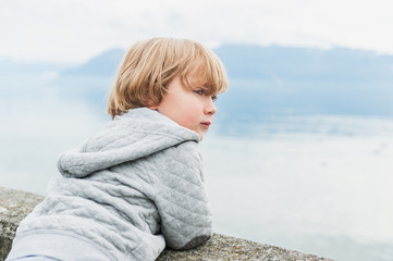 Adorable toddler boy resting by the lake on a fresh day