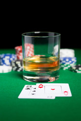 close up of chips, cards and whisky glass on table