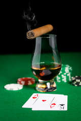 close up of chips, cards whisky and cigar on table